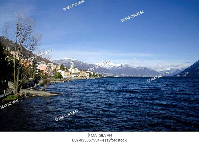 Alpine village on the lakefront with snow-capped mountain and blue sky with clouds