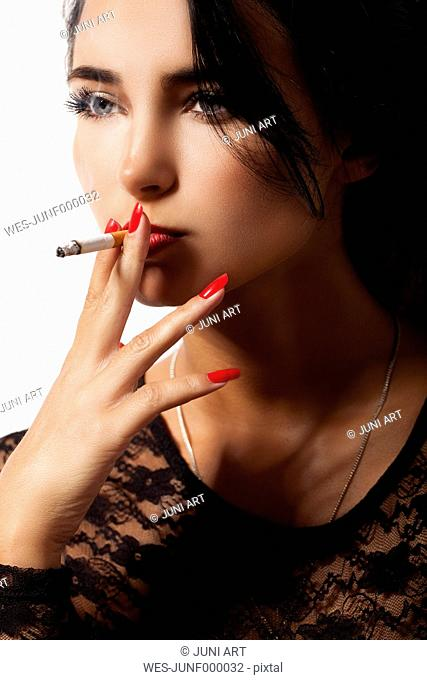 Portrait of smoking young woman with red nail polish