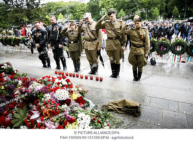 09 May 2019, Berlin: People in traditional uniforms salute the Soviet memorial at the Tiergarten on the occasion of the 74th anniversary of Russia's victory in...