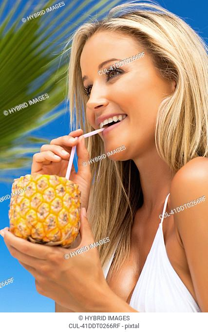 Woman drinking from pineapple outdoors