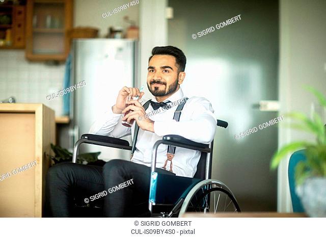 Businessman having drink in wheelchair