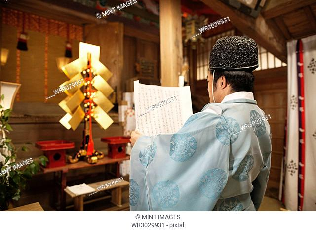 Rear view of priest holding scroll at Shinto Sakurai Shrine, Fukuoka, Japan