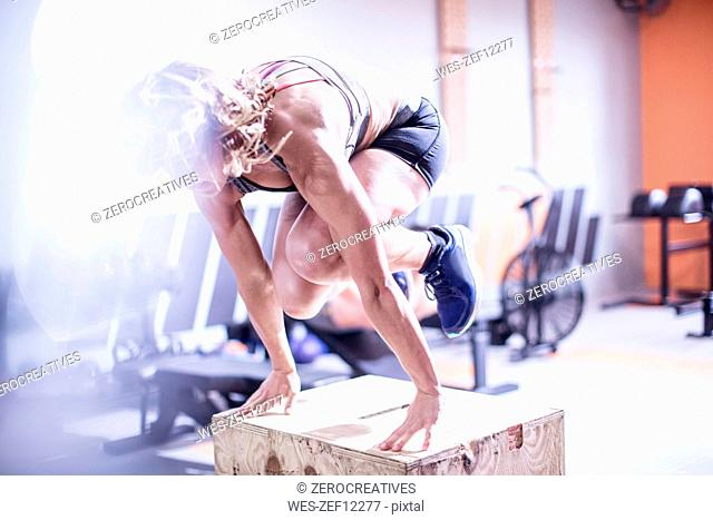 Young woman in gym doing box jumps