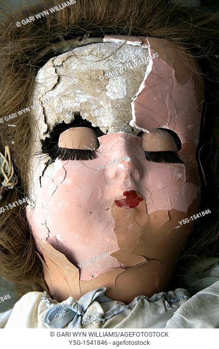 old dirty damaged girl doll head in window