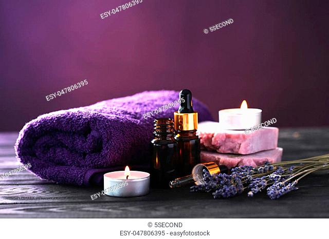 Lavender oil with soap and flowers on black wooden table