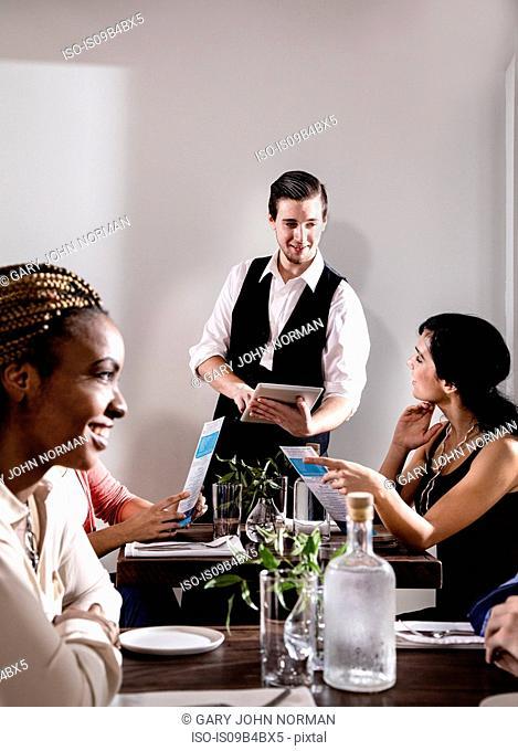 Waiter serving diners in restaurant, waiter using digital tablet