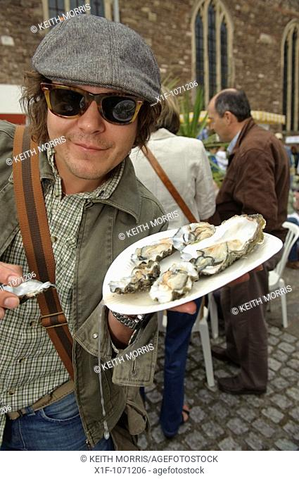 A man eating fresh oysters at the Abergavenny food festival, Monmouthshire south wales UK  September 19 2009