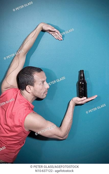 Hispanic man posing with a bottle of beer