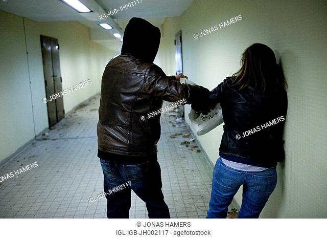 This picture shows a man following a woman in a covered passage as he tries to rape or steal the bag