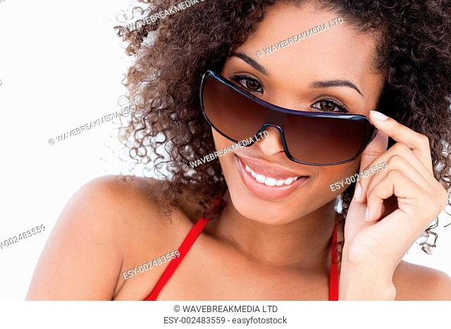 Smiling young brunette looking over her sunglasses against a white background