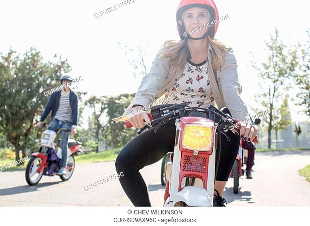 Group of friends riding mopeds along road, young female rider in foreground