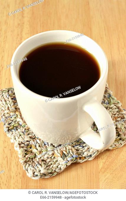 White mug with black mocca coffee. Mug sitting on hand-knit coaster