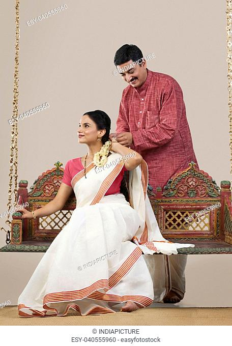 South Indian man tying a Gajra on his wife's hair
