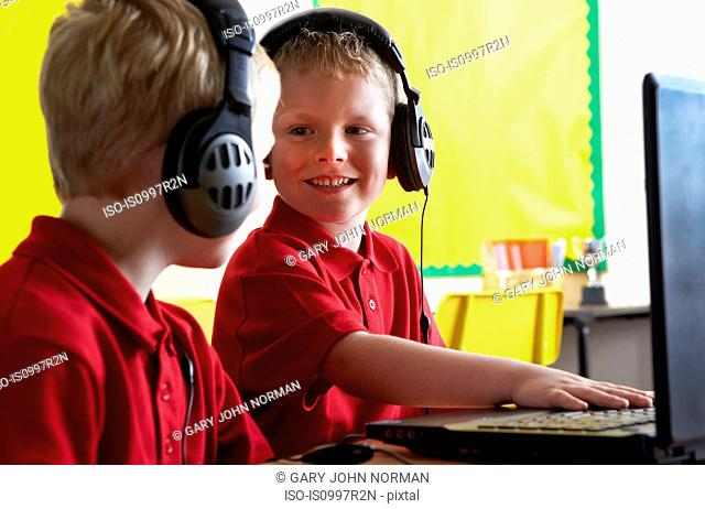 School boys wearing headphones and looking at computer in classroom