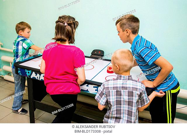 Caucasian children playing air hockey