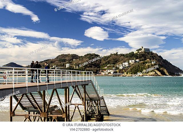 People gather on the bridge to admire the beautiful view of Santa Clara Island in the city of San Sebastian