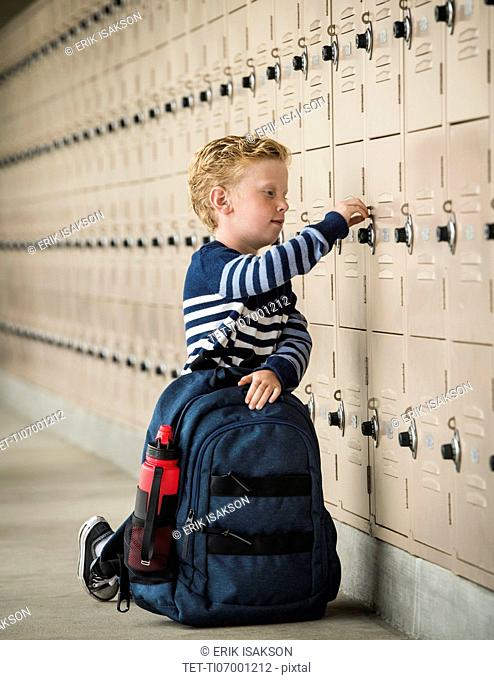 Boy with backpack by school lockers