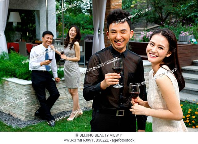 Young people holding glasses of red wine outside