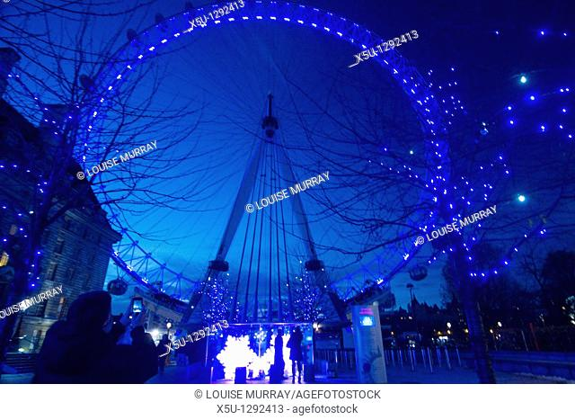 London Eye on the South bank of the Thames being photographed by tourist with smartphone