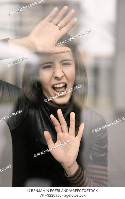 portrait of angry woman yawning behind glass window, in Munich, Germany