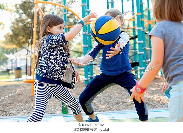 Children playing basketball in playground