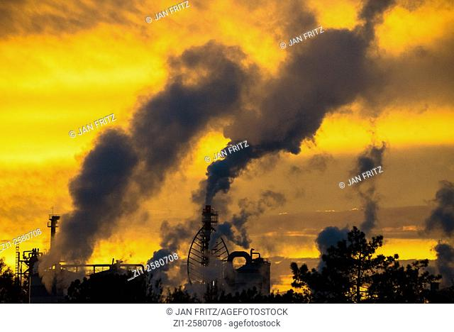 black smoke from plant against orange yellow sky of sunset