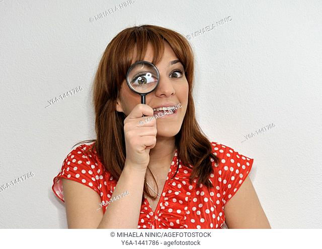 Young woman looking trough magnifying glass