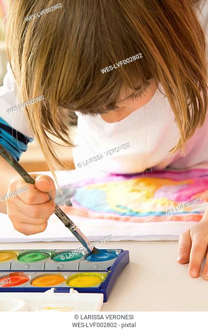 Little girl painting with watercolours