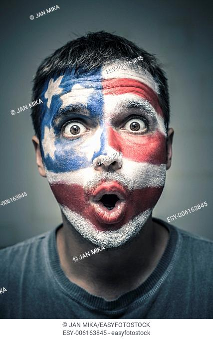 Portrait of surprised man with US flag painted on face