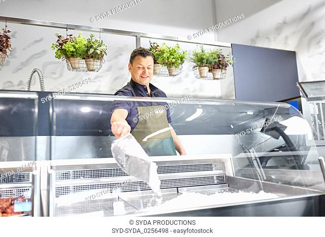 male seller adding ice to fridge at grocery store