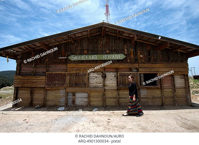 A woman walks in front of the old ticket office at the Ifrane Ski Club in Ifrane, Morocco