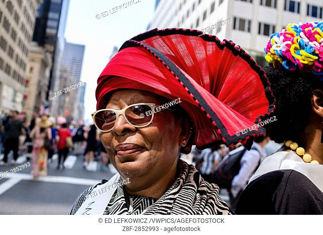 New York, NY - April 16, 2017. A woman from The Milliners Guild wearing a red a black hat at New York's annual Easter Bonnet Parade and Festival on Fifth Avenue