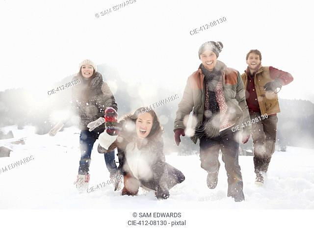 Portrait of friends playing in snowy field