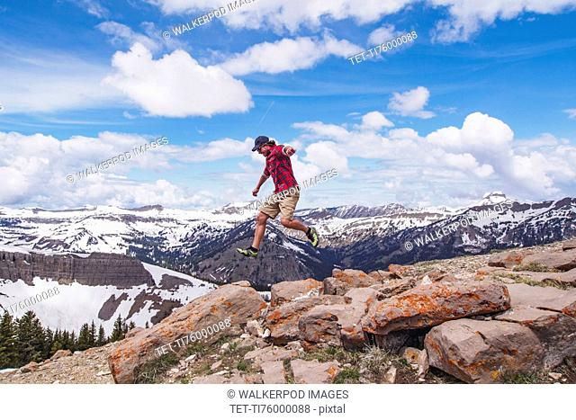 Mid adult man jumping over rocks in mountains