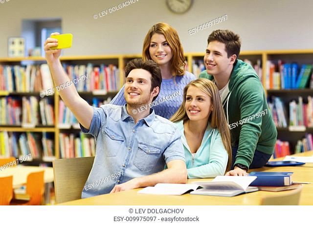 people, technology, friendship, education and school concept - group of happy students with smartphone taking selfie at library