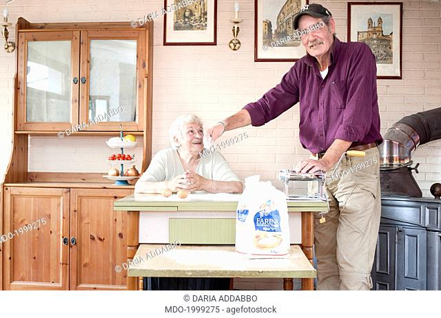 Old man standing beside a draw-leaf table in the kitchen and pouring the flour on it to make fresh pasta. Beside him, a smiling old woman sitting and looking at...