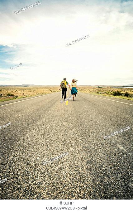 Rear view of young couple running hand in hand on road, Cody, Wyoming, USA