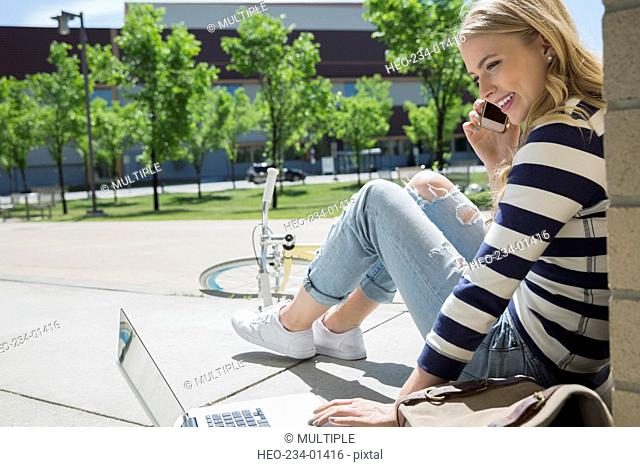 College student using laptop and cell phone campus