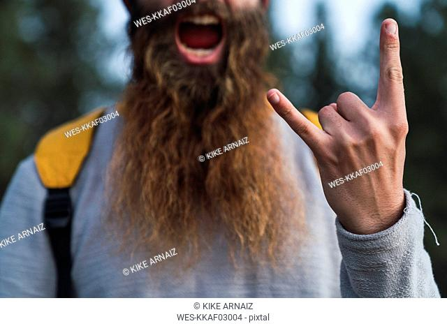 Close-up of screaming man with beard making horn sign
