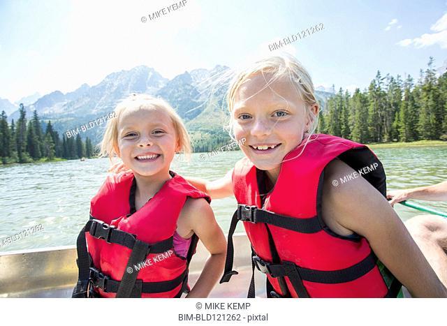 Caucasian girls wearing life jackets in canoe