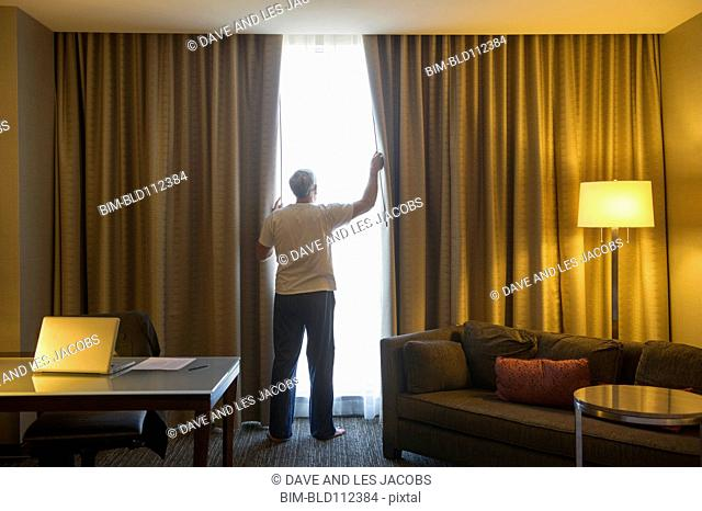 Older Caucasian man opening hotel curtains