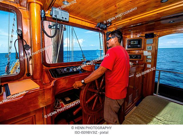 Captain of a boat navigating his old schooner from the ship's wheel, Komodo Island, East Nusa Tenggara, Indonesia