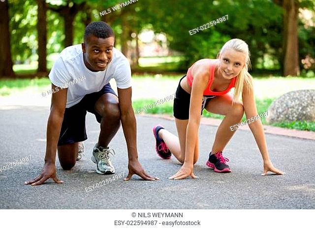 zwei sportliche junge jogger laufend im park im sommer