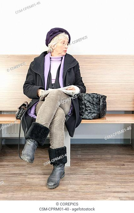 Woman with bandaged arm, sitting in the waiting room of a medical practice