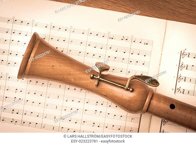 Close up of wooden recorder and notes on paper. Concept of playing the flute, music and melody