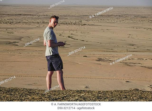 A young man at the controls of a drone in the Namibian desert. Solitaire, Namibia