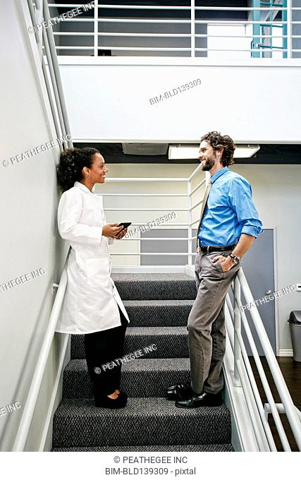 Doctor and businessman talking on staircase
