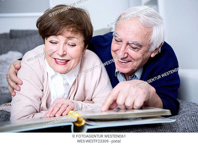 Senior couple lying on couch, looking at photo album