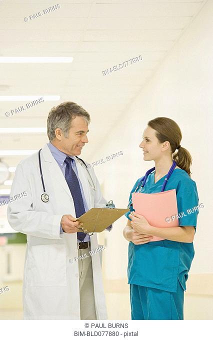 Doctor talking to nurse in hospital hallway