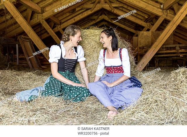 Two girlfriends with dirndl talk on the hayloft